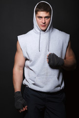 Male boxer in a hood standing over a black background.