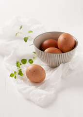 Brown eggs in a bowl and twigs of oregano on white cheesecloth. Selective focus.