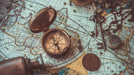 Old collection compass, telescope and collecting rare items on antique world map. (vintage style)