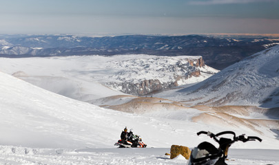 Couple on a snowmobile on a plateau in the mountains. State Nature Reserve in Adygea, Russia.