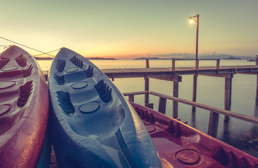 Sunset red and blue kayak boats moored in the sea port. (vintage style)