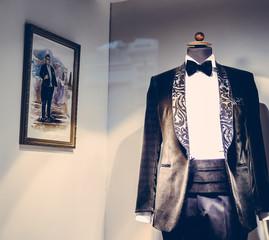 Wedding dress shop, black suit for groom and men on mannequin in showroom, vintage