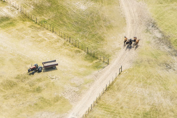 Aerial view of a farm field with tractor and horses