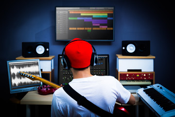 back of male musician playing guitar in recording studio for music background