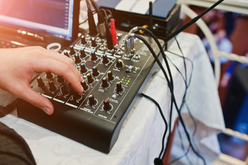 Hand of man on digital mixing console. Sound mixer control panel