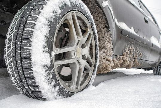 Wheel on snowy winter road. Car tire