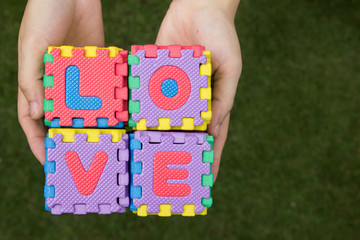 Puzzle wording love has hold on hand with green background
