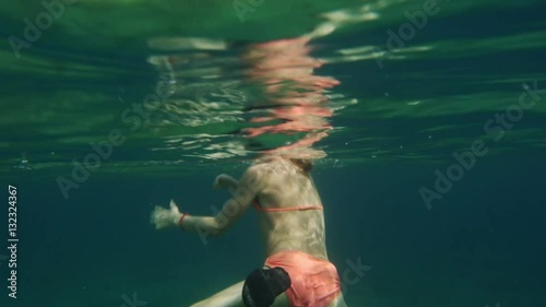 """""""preteen girl swimming and diving in water, shot taken with underwater camera underneath surface."""" Stock foota"""