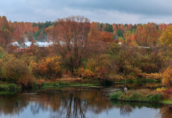 lonely fisherman on the autumn river