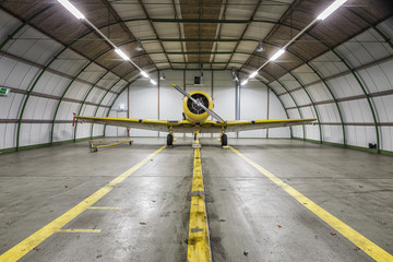 Vintage old yellow war plane inside of a empty hangar