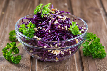 Red cabbage salad with parsley sprinkled with nuts, wooden background