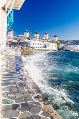 Splashing waves and famous Mykonos windmills in golden afternoon light, Mykonos island, Cyclades, Greece
