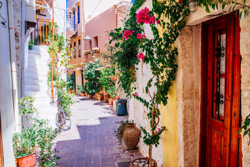 Colorful streets of old Chania town with blooming flowers and ancient stone, Crete, Greece.