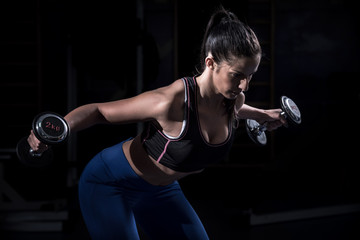 Woman bodybuilder  lifting dumbbell isolated over black background