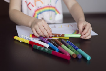 kids  draw rainbows and write the word happiness, kids hands  drawing