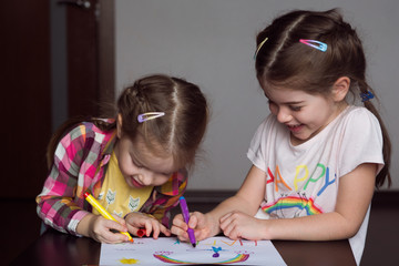 Happy cute kids draw  rainbows and write the word happiness, small  artists paint  rainbow
