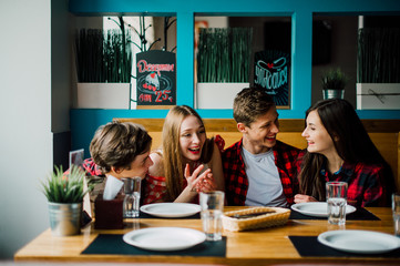Group of young friends hanging out at a coffee shop. Young men and women meeting in a cafe having fun and drinking coffee. Lifestyle, friendship and urban life concepts.
