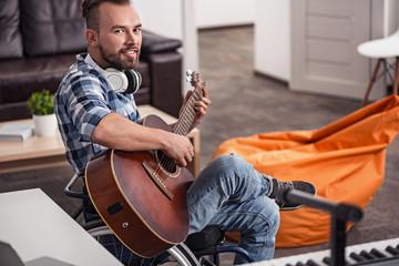 Incapacitated young man posing with his guitar