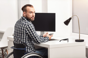 Young physically challenged person working in home office