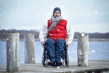 Mann mit Handicap im Rollstuhl am See
