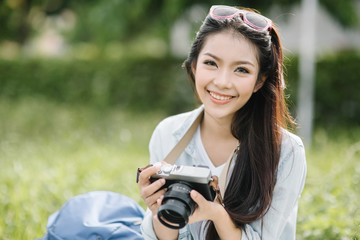 Portrait of beautiful young smiling Asia woman with camera at summer green park,travel concept