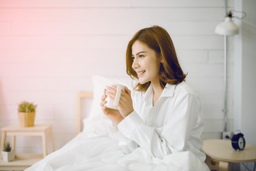 Beautiful Asia woman at her bedroom drinking tea in the morning.