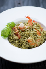 Closeup of spinach risotto with tiger shrimps and tomatoes
