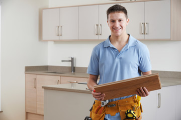 Portrait Of Carpenter Installing Fitted Kitchen