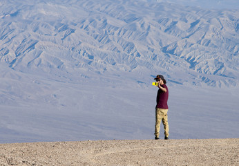 One young man takes a photo in the desert with a smartphone from the edge of the valley. He stands against a blue hue mountain texture, lighted by soft light.