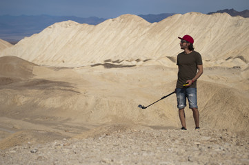 One young man stands in the desert holding a smartphone and an action camera, looking to the left from the edge of the valley, against a white sandstone natural texture