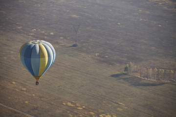 Blue and yellow balloon soaring in the sky over the fields