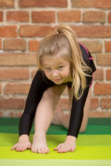 Happy girl stretching on mats