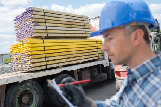 Man with clipboard next to lorry delivering timber