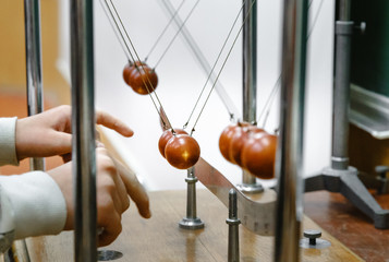 Experiment with balls in laboratory. Research concept. Conservation of energy. Simple Pendulums. When pendulum moving towards the mean position the potential energy is converted to kinetic energy.