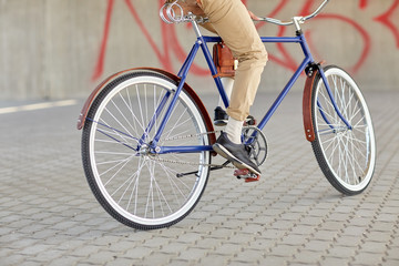 close up of hipster man riding fixed gear bike