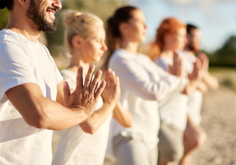 Wall Murals Martial arts group of people making yoga or meditating on beach