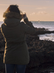 A women taking pictures on her mobile phone of dolphins jumping out of the water .