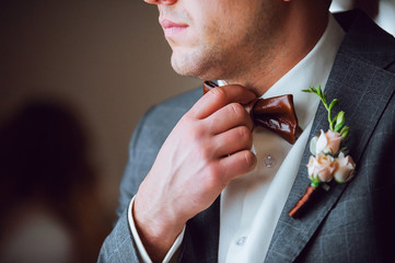 groom straightens his bow tie