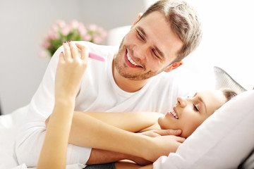 Happy couple with pregnancy test in bed