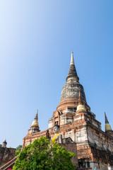 Buddha statue at the bottom of a large ancient pagoda on blue sky background at Wat Yai Chai Mongkon temple in Phra Nakhon Si Ayutthaya Historical Park, Ayutthaya Province, Thailand