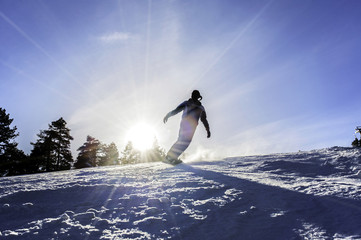 Snowboarding, silhouettes of snowboarders on the ski slope with the sun's rays on a blue sky, lens flare