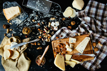 Cheeseboard. Variety of cheeses with nuts, honey, olives on black background. Top view