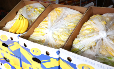 Fresh bananas in cardboard boxes on market