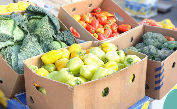 Fresh vegetables in cardboard boxes on market
