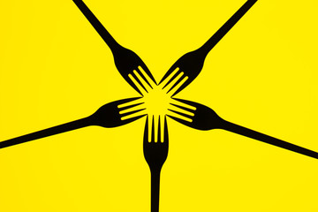 Silhouette of forks on yellow  background