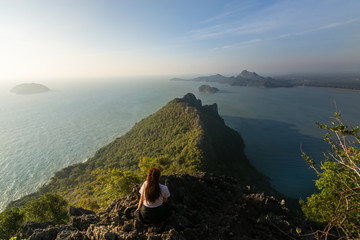 A female hiker was sitting near the edge watching sunset in Thailand looking on to the gulf of Thailand. This is one of the tourist attraction.