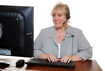 Mature customer service representative with headset working at the computer with a customer problem