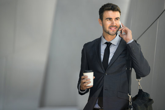 Professional with coffee and cell phone candid action in motion handsome businessman