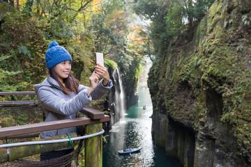 Woman taking selfie by cellphone in Takachiho gorge