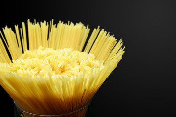 Fusilli pasta and spaghetti in glass on a black background with clipping path.